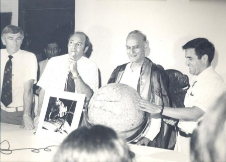 The astronauts present an autographed model of the moon to the students of Karachi University, as the Vice Chancellor Hussain looks on.