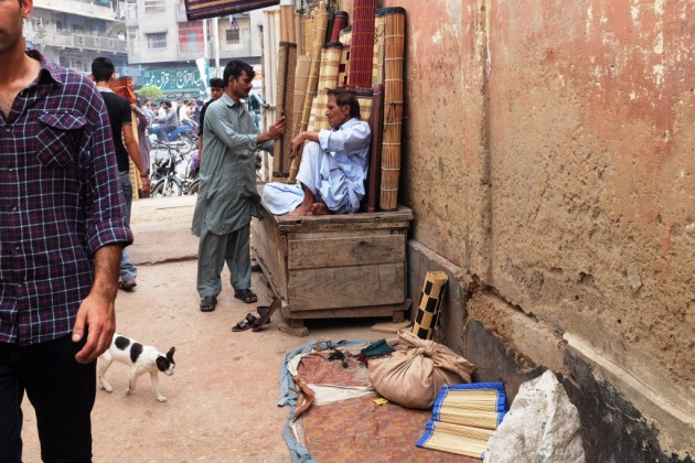 31 - Mehboob who has tiny shop for cane blinds speaks with a fellow worker