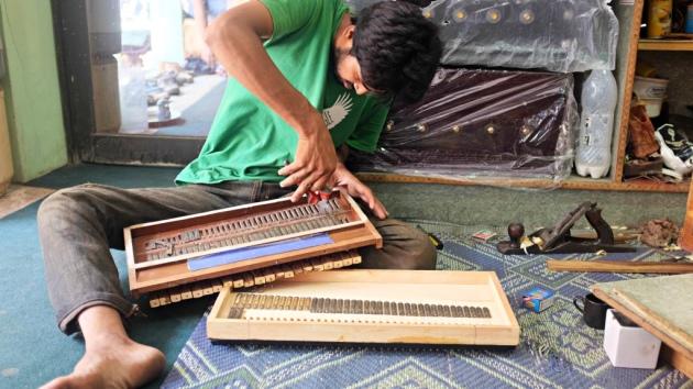 1 - A worker repairs a harmonium