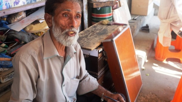 3 - Waheed answers a question while repairing harmonium